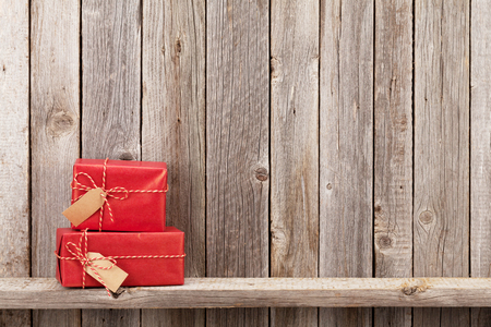 Foto per Christmas gift boxes in front of wooden wall. View with copy space - Immagine Royalty Free