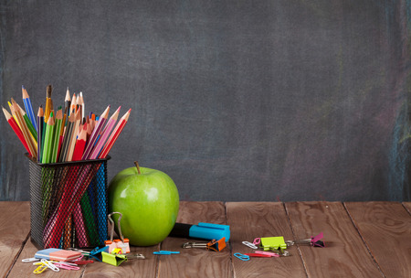 Photo for School and office supplies on classroom table in front of blackboard. View with copy space - Royalty Free Image