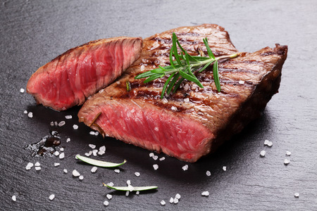 Photo for Grilled beef steak with rosemary, salt and pepper on black stone plate - Royalty Free Image