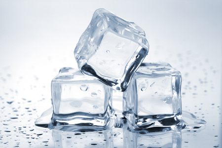 Three melting ice cubes on glass table