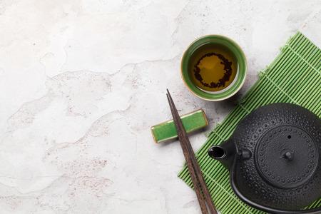 Photo pour Asian tea bowl and teapot over stone table. Top view with copy space - image libre de droit