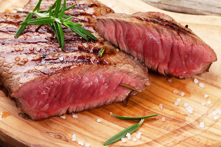 Photo for Grilled beef steak with rosemary, salt and pepper on cutting board - Royalty Free Image