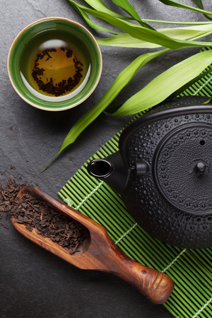 Photo for Asian tea bowl and teapot over stone table - Royalty Free Image