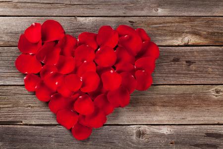 Foto de Red rose petals heart over wooden table. Top view with copy space - Imagen libre de derechos
