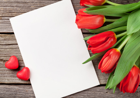 Photo for Red tulips, blank greeting card and candy hearts over wooden table. Valentines day background. Top view with copy space - Royalty Free Image