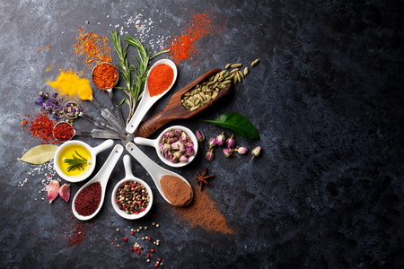 Photo pour Herbs and spices over black stone background. Top view with copy space - image libre de droit