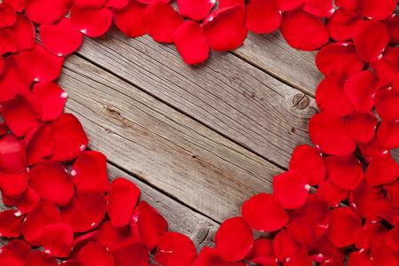 Photo pour Red rose petals heart over wooden table. Top view with copy space - image libre de droit