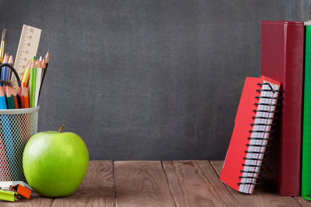 Photo pour School and office supplies and apple on classroom table in front of blackboard. View with copy space - image libre de droit
