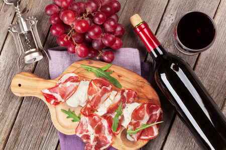 Photo for Prosciutto and mozzarella with red wine on wooden table. Top view - Royalty Free Image
