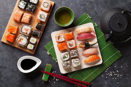 Photo pour Set of sushi and maki roll and green tea on stone table. Top view - image libre de droit