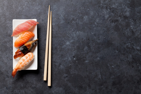 Foto de Sushi set and chopsticks on stone table. Top view with copy space - Imagen libre de derechos