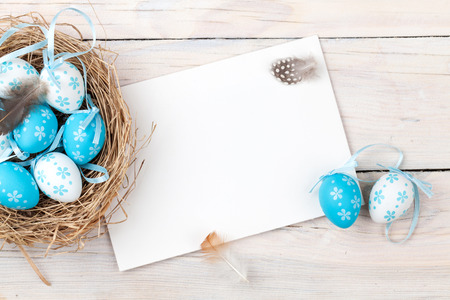 Photo pour Easter background with blue and white eggs in nest and greeting card over white wood. Top view with copy space - image libre de droit