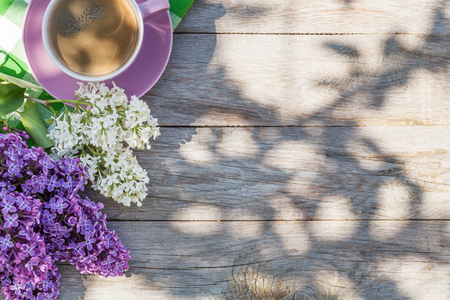 Photo pour Coffee cup and colorful lilac flowers on garden table. Top view with copy space - image libre de droit