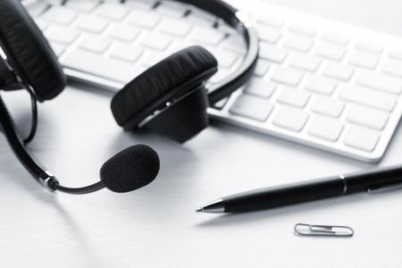 Foto de Office desk with headset and pc. Call center support table. Blue toned - Imagen libre de derechos