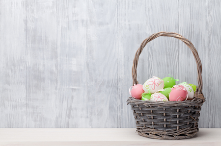 Photo for Easter eggs in basket on shelf in front of wooden wall. View with copy space - Royalty Free Image