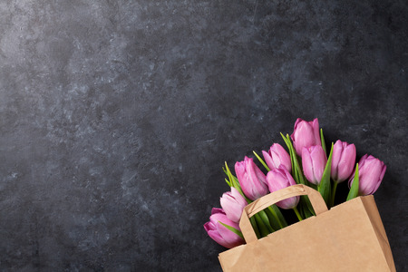 Photo for Fresh pink tulip flowers in paper bag on dark stone table. Top view with copy space - Royalty Free Image