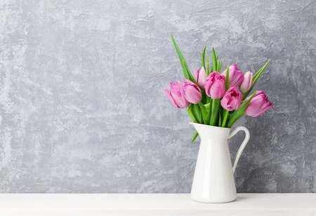 Photo pour Fresh pink tulip flowers bouquet on shelf in front of stone wall. View with copy space - image libre de droit