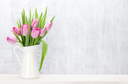 Photo pour Fresh pink tulip flowers bouquet on shelf in front of wooden wall. View with copy space - image libre de droit