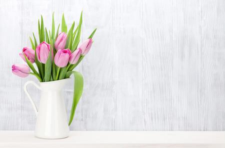 Foto de Fresh pink tulip flowers bouquet on shelf in front of wooden wall. View with copy space - Imagen libre de derechos