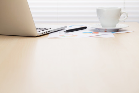 Photo pour Office workplace with with laptop and coffee on wooden desk table in front of window with blinds. Focus on cup. View with copy space - image libre de droit