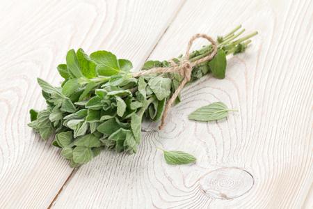 Foto de Bunch of garden oregano herb on wooden table - Imagen libre de derechos