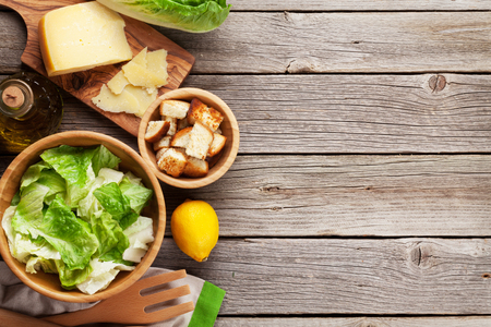Photo pour Fresh healthy caesar salad cooking on wooden table. Top view with copy space - image libre de droit