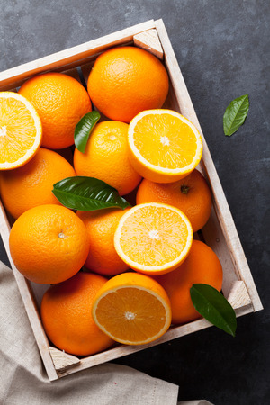 Photo for Fresh ripe oranges in wooden box on dark stone background. Top view - Royalty Free Image