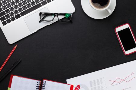 Foto de Office leather desk table with laptop, coffee cup, notepad and phone. Top view with copy space - Imagen libre de derechos