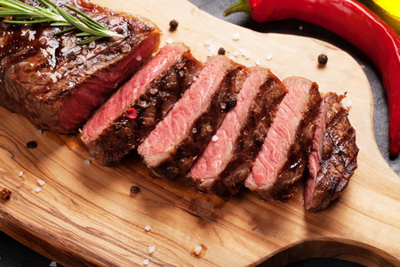 Photo for Grilled striploin sliced steak on cutting board over stone table - Royalty Free Image