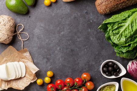 Foto de Cooking food ingredients. Lettuce salad, avocado, olives, cheese, bread and tomato cherry over stone background. Top view with copy space - Imagen libre de derechos