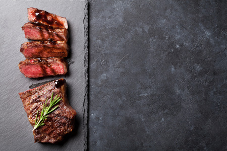 Photo for Grilled sliced beef steak with balsamico and rosemary on stone table. Top view with copy space - Royalty Free Image