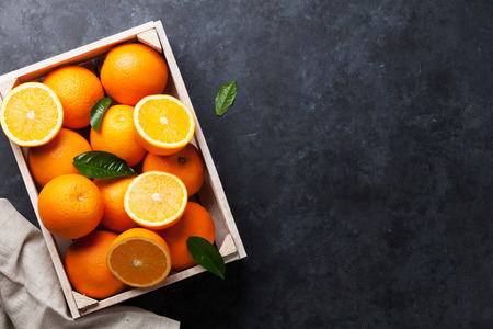 Photo pour Fresh orange fruits in wooden box on stone table. Top view with copy space - image libre de droit