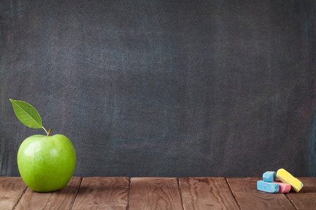 Photo pour Apple fruit and chalks on classroom table in front of blackboard. View with copy space - image libre de droit