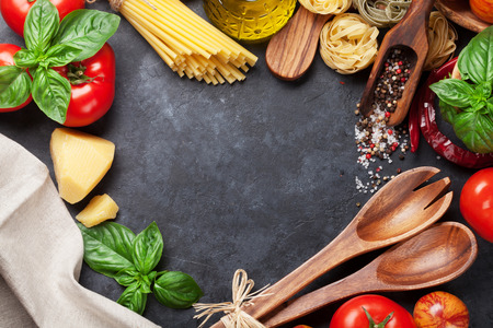 Photo pour Italian food cooking. Tomatoes, basil, spaghetti pasta, olive oil and chili pepper on stone kitchen table. Top view with copy space for your recipe - image libre de droit