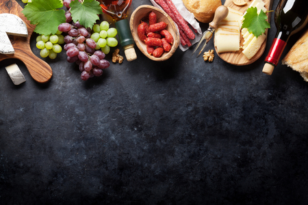 Foto de Red and white wine bottles, grape, cheese and sausages over stone table. Top view with copy space - Imagen libre de derechos