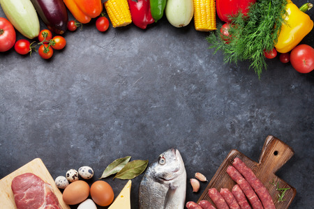 Photo pour Vegetables, fish, meat and ingredients cooking. Tomatoes, eggplants, corn, beef, eggs, cheese. Top view with copy space on stone table - image libre de droit