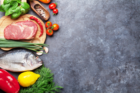 Photo for Vegetables, fish, meat and ingredients for cooking. Tomatoes, pepper, corn, beef, eggs. Top view with copy space on stone table - Royalty Free Image