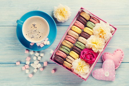 Photo pour Colorful macaroons, coffee and marshmallow on wooden table. Sweet macarons in gift box and hearts. Top view. Retro toned - image libre de droit