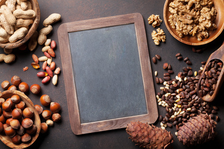 Photo for Various nuts on stone table. Top view with chalkboard for copy space - Royalty Free Image