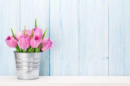 Photo for Fresh pink tulip flowers bouquet on shelf in front of wooden wall. View with copy space - Royalty Free Image