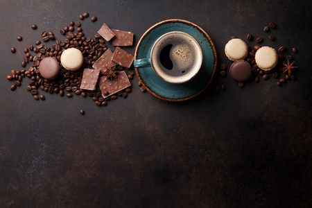 Photo for Coffee cup, beans, chocolate and macaroons on old kitchen table. Top view with copyspace for text - Royalty Free Image