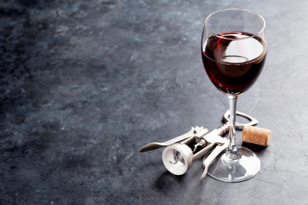 Foto de Red wine glass and corkscrew on stone table. With copy space - Imagen libre de derechos