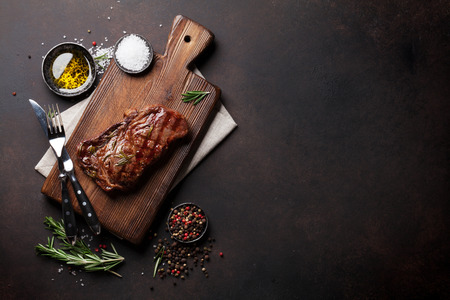 Photo for Grilled ribeye beef steak, herbs and spices. Top view with copy space for your text - Royalty Free Image