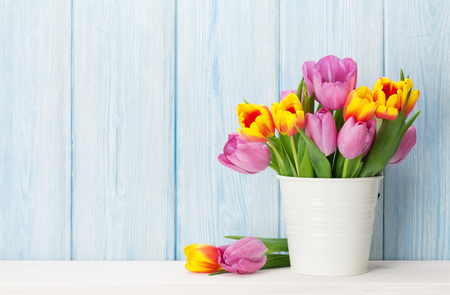 Photo for Fresh colorful tulip flowers bouquet on shelf in front of wooden wall. View with copy space - Royalty Free Image
