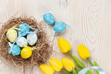 Photo for Easter background with eggs in nest and yellow tulips over white wooden table. Top view - Royalty Free Image