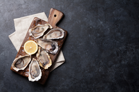 Photo pour Opened oysters, ice and lemon on wooden board over stone table. Half dozen. Top view with copy space - image libre de droit