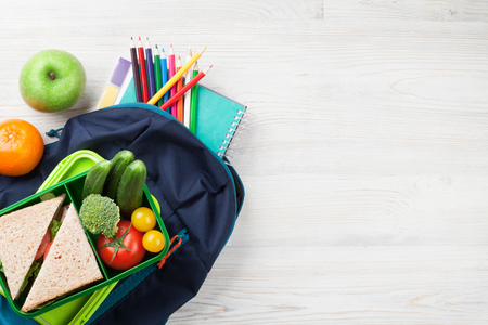 Photo pour Lunch box with vegetables and sandwich on wooden table. Kids take away food box and school backpack. Top view with copy space - image libre de droit