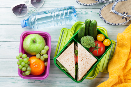 Photo for Lunch box with vegetables and sandwich on wooden background. Beach take away food box, towel and glasses. Top view - Royalty Free Image