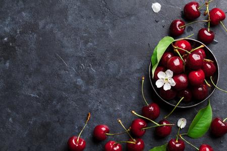Photo pour Fresh garden cherry in bowl on stone table. Top view with copy space - image libre de droit