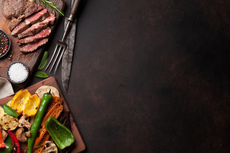 Photo pour Beef steak and grilled vegetables on cutting board on stone table. Top view with copy space - image libre de droit